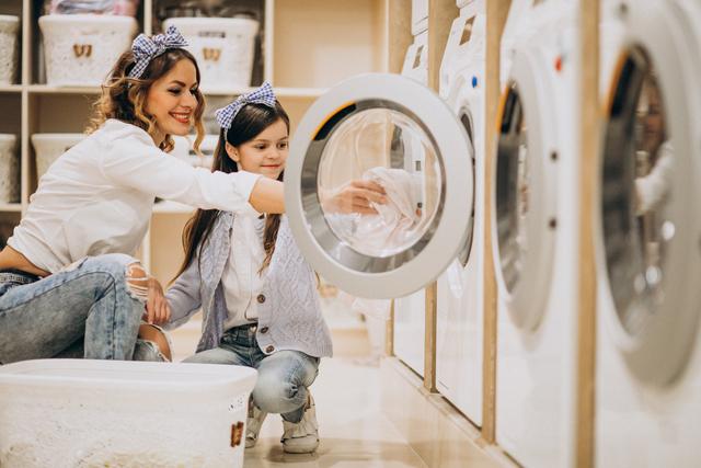 mãe e filha colocando peças na secadora de roupa a gás