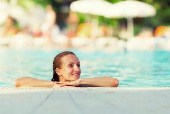 mulher nadando representando como aquecer uma piscina